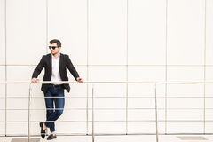 Glamour man. Portrait of young trendy man with black glasses is posing in modern office Stock Images