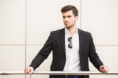 Glamour man. Portrait of young trendy man is posing in front of a wall Royalty Free Stock Photos
