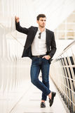 Glamour man. Portrait of young trendy man with is posing in modern office Royalty Free Stock Photos