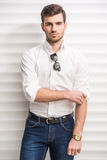 Glamour man. Portrait of young trendy man with is posing in modern office Royalty Free Stock Photo