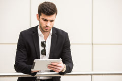 Glamour man. Portrait of young trendy man with tablet is posing in front of a wall Royalty Free Stock Photography