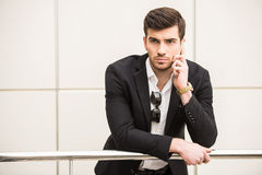 Glamour man. Portrait of young trendy man is talking by phone Stock Images
