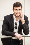 Glamour man. Portrait of young trendy man is talking by phone and looking at the camera Stock Photo