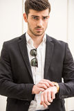 Glamour man. Young trendy man is posing with watch in front of a wall Royalty Free Stock Photo