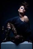 Glamour model. Posing against dark background Royalty Free Stock Photos