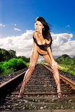 Glamour model. Poses on train tracks with deep blue sky in background Royalty Free Stock Image
