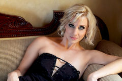 Glamour model with black evening dress lying on a modern Victorian couch Royalty Free Stock Image