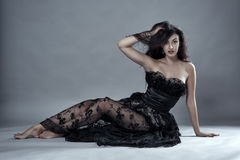 Glamour model in black lace dress. Gorgeous beauty model in black lace dress on gray background Royalty Free Stock Image