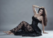Glamour model in black lace dress. Gorgeous beauty model in black lace dress on gray background Stock Photography