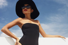 Glamour model in hat under sun Stock Photography