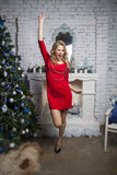 Glamour model in red party dress near New year tree Stock Photography