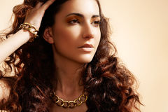 Glamour model with shiny gold jewelry, volume hair stock image