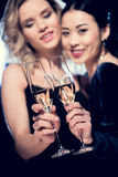 Glamour multicultural girls toasting with champagne glasses at party Stock Photography