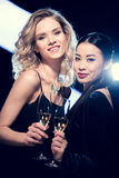 Glamour multiethnic girls toasting with champagne glasses and looking at camera at party Royalty Free Stock Images