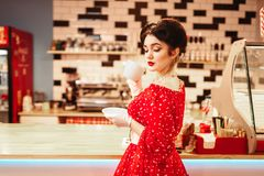 Glamour pin up girl drinks coffee in retro cafe. Glamour pin up girl with make-up drinks coffee in retro cafe, 50 american fashion. Red dress with polka dots Royalty Free Stock Image