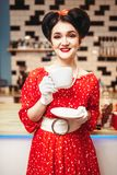 Glamour pin up girl drinks coffee in retro cafe. Glamour pin up girl with make-up drinks coffee in retro cafe, 50 american fashion. Red dress with polka dots Stock Images
