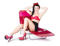 Glamour pin-up girl. Retro summer fashion. Glamour pin-up girl relaxing on pink holiday recliner chair in high class heels and polkadot brassiere. Retro summer Stock Image