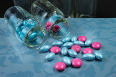 Glamour pink and blue pills on blue background Stock Image