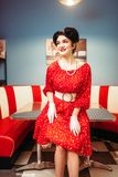 Glamour pinup girl with makeup, retro cafe. Interior, 50 american fashion. Red dress with polka dots, vintage style Royalty Free Stock Photos