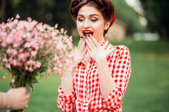 Glamour pinup girl takes gift a bouquet of flowers stock images