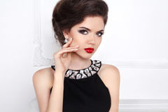 Glamour portrait of beautiful woman model with red lips and hair. Styling in luxury fashion jewels Royalty Free Stock Photography