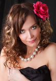 Glamour Portrait of beautiful young woman with Red flower. In brown long ringlets hair Stock Photography