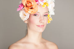 Glamour portrait with flowers. Portrait of smiling young girl with her hair covered completely with roses and other flowers Royalty Free Stock Image