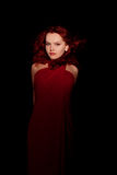 Glamour portrait redhaired woman. In a red dress on black background Stock Photography