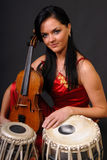 Glamour portrait of sexy woman with violin. And two drums. black background Royalty Free Stock Photography
