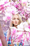 Glamour portrait of sexy young woman in blooming pink flowers Royalty Free Stock Images