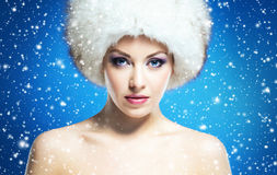 Glamour portrait of a young and beautiful woman in a winter hat. Portrait of a young and beautiful woman in a winter hat on a blue background with falling Stock Images
