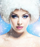 Glamour portrait of a young and beautiful woman in a winter hat. Portrait of young and beautiful woman in winter hat over blue background with a falling Royalty Free Stock Image