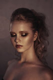 Glamour portrait of young fashion woman face with bright evening golden make up for party and tanned skin. Warm toning. Retouched Royalty Free Stock Photography