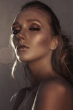 Glamour portrait of young fashion woman face with bright evening golden make up for party and tanned skin. Warm toning. Retouched Royalty Free Stock Image