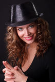 Glamour portret of beauty woman smiling in dark hat with pistol. Glamour portret of beauty woman smiling in dark hat make a joke pistol with her fingers stock photo