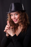 Glamour portret of beauty woman smiling in dark hat with pistol. Glamour portret of beauty woman smiling in dark hat make a joke pistol with her fingers royalty free stock photo