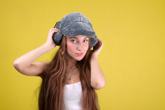 Glamour russian woman and fur-cap. On yellow background royalty free stock photography