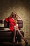 Glamour woman. Beautiful blond glamour woman in red dress sitting on sofa in luxury retro interior Royalty Free Stock Images