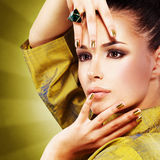 Glamour woman with beautiful golden nails and emerald ring Royalty Free Stock Photos