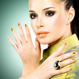 Glamour woman with beautiful golden nails and emerald ring stock images