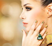 Glamour woman with beautiful golden nails and emerald ring Stock Photography