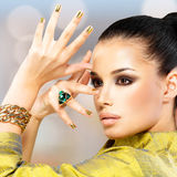 Glamour woman with beautiful golden nails and emerald ring Stock Photos