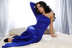 Glamour woman with dark hair wearing elegant blue dress Stock Photography