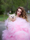 Glamour woman with dog. Young woman with beautiful face and long curly hair in glamour pink dress holding cute small dog outdoor Royalty Free Stock Photography