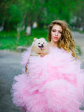 Glamour woman with dog. Young woman with beautiful face and long curly hair in glamour pink dress holding cute small dog outdoor with green trees Royalty Free Stock Photography