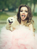 Glamour woman with dog. Young woman with beautiful face and long curly hair in glamour pink dress showing tongue holding cute small dog outdoor Royalty Free Stock Photo