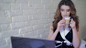 Glamour woman drinking latte and working with laptop in cafe stock video