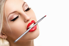Glamour woman with makeup brash. Glamour blond young woman with clossing eyes and makeup brash in the mouth on white background Royalty Free Stock Images
