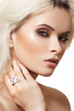 Glamour woman model with fashion makeup, jewellery. Beauty portrait of model face with smoky-eyes make-up and big white cocktail ring. Blond hair Stock Photos