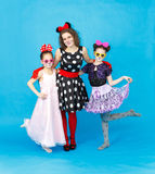 Glamour woman and two girls in party costumes on blue background Stock Photo